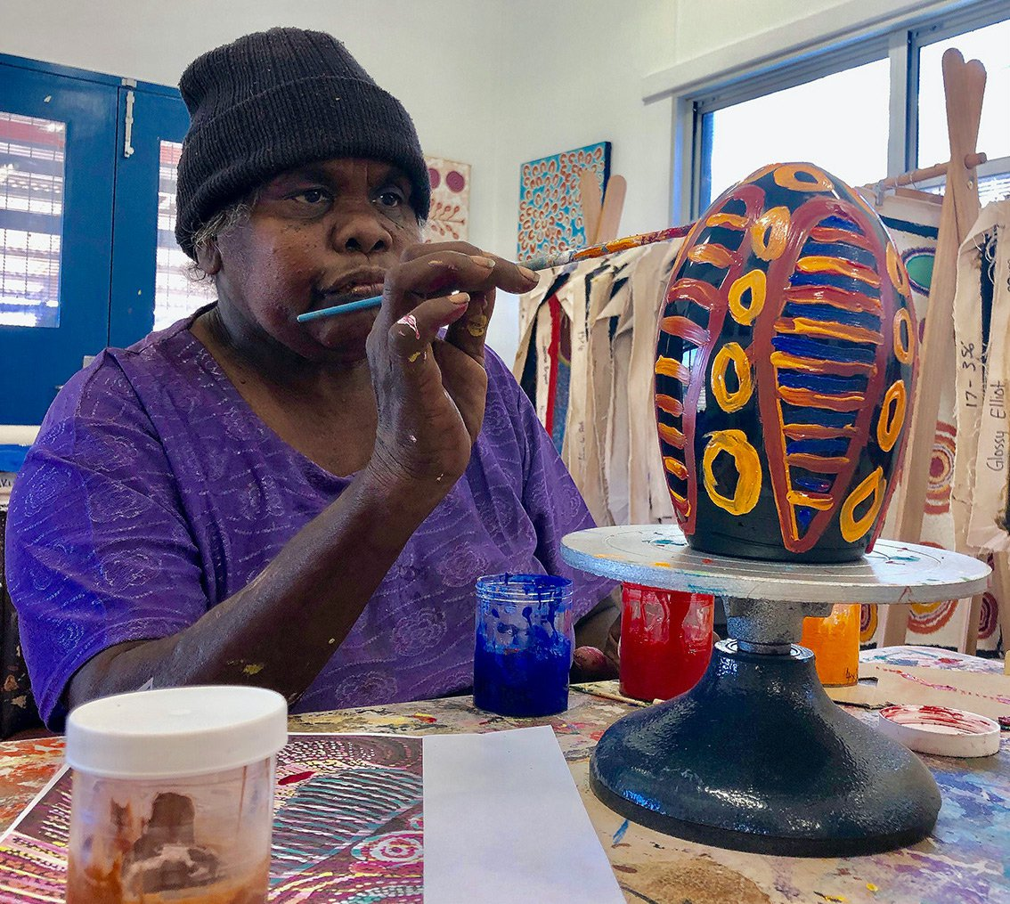 Ruth Fatt painting glass in the studio. Image courtesy of Ninuku Arts